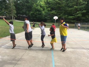 Day Campers play a traditional rubber band jump rope game.