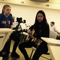 Josephana warms up on the guitar before leading the youth in singing